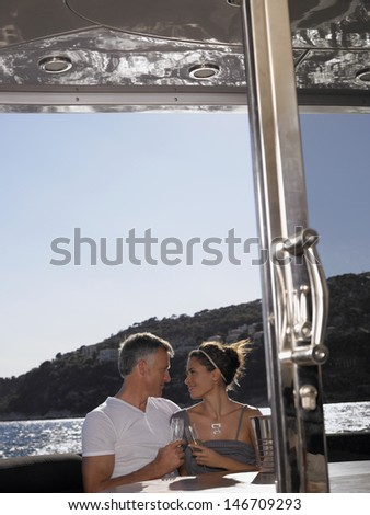 Affectionate couple looking at each other while having champagne on yacht - stock photo