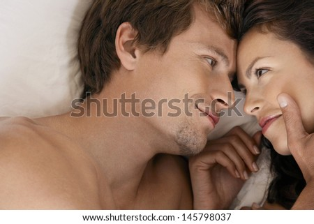 Affectionate couple lying in bed looking at each other - stock photo