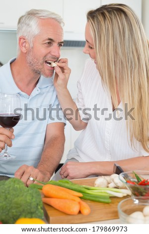 Affectionate couple preparing dinner together and drinking red wine at home in the kitchen - stock photo