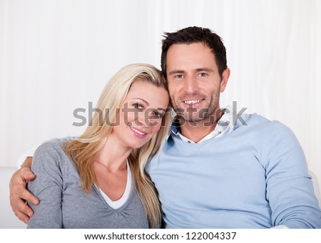 Affectionate couple relaxing on a sofa with the mans arm around his wifes shoulders as she rests her head on his shoulder - stock photo