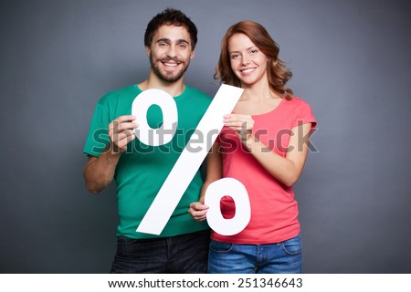 Affectionate couple showing percentage symbol - stock photo