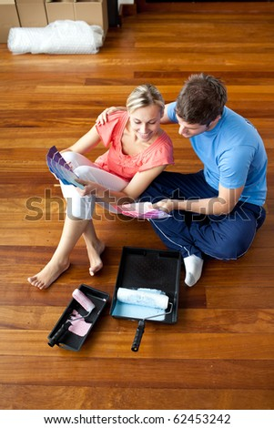 Affectionate couple sitting on the floor picking colors - stock photo