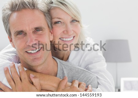 Affectionate couple smiling at camera at home in bedroom - stock photo