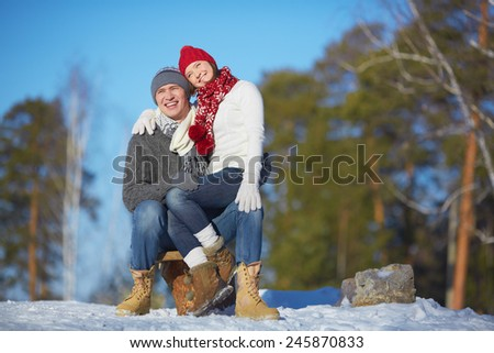Affectionate couple spending leisure in winter park - stock photo