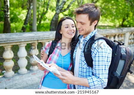Affectionate couple studying map of ancient town while on travel - stock photo