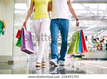 Affectionate couple with bags shopping in trade center - stock photo