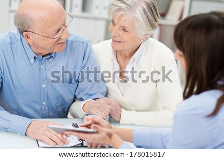 Affectionate elderly couple in a business meeting holding hands as they discuss a proposal put forward by their broker - stock photo