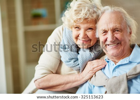 Affectionate elderly man and woman looking at camera - stock photo