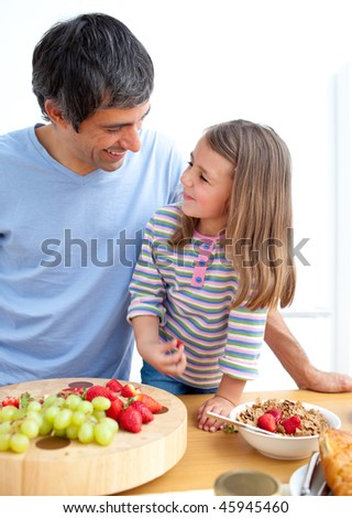 Affectionate father and his daughter having breakfast in the kitchen - stock photo