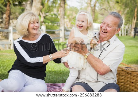 Affectionate Granddaughter and Grandparents Playing Outside At The Park. - stock photo