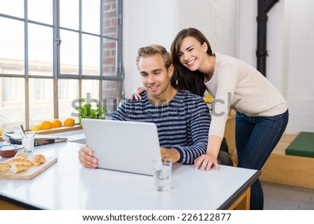 Affectionate happy couple using a laptop computer on their kitchen counter spread with frosh rolls and fruit as they sit and stand arm in arm - stock photo