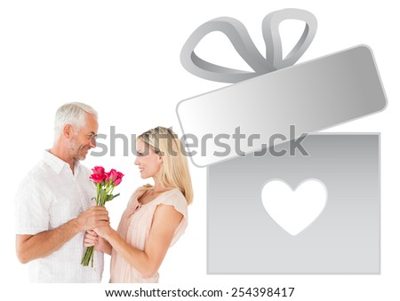 Affectionate man offering his partner roses against gift with heart - stock photo