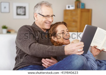Affectionate middle-aged couple relaxing on a sofa together at home laughing at something on a tablet computer, natural and spontaneous - stock photo