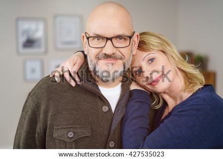 Affectionate middle-aged couple with friendly smiles posing arm in arm in their living room looking at the camera, close up head and shoulders portrait - stock photo