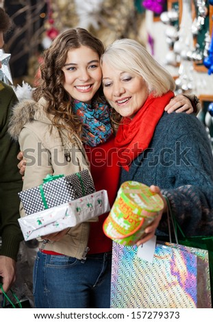 Affectionate mother and daughter with Christmas presents standing at store - stock photo