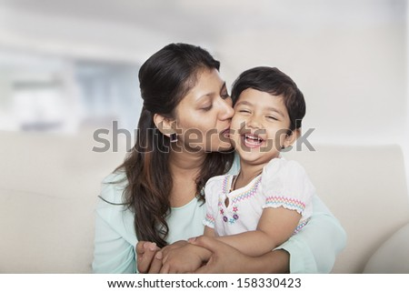 Affectionate mother holding and kissing her daughter - stock photo