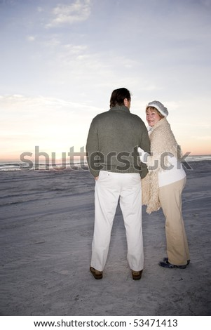 Affectionate senior couple in sweaters on beach at dawn - stock photo