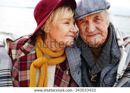 Affectionate senior couple in warm clothes - stock photo