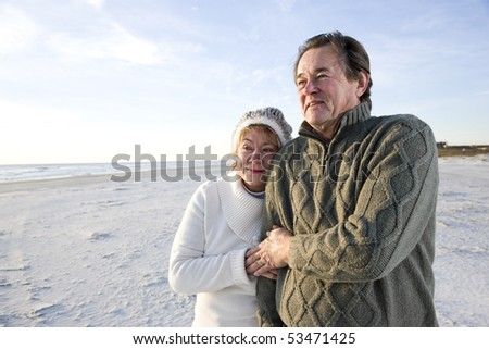 Affectionate senior couple in warm clothing standing together on beach - stock photo
