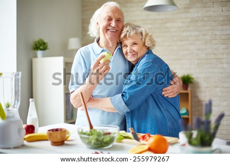 Affectionate seniors in embrace looking at camera - stock photo