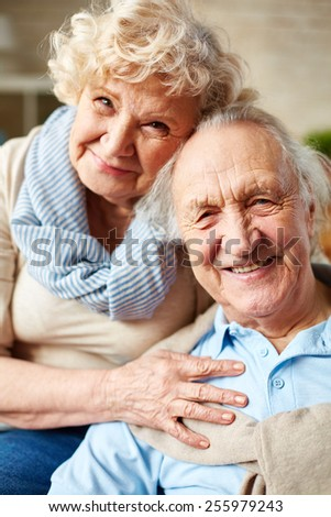 Affectionate seniors looking at camera with smiles - stock photo
