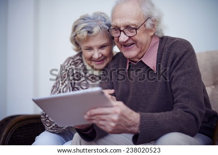 Affectionate seniors spending leisure in internet using touchpad - stock photo