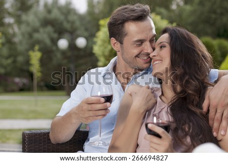 Affectionate young couple having red wine in park - stock photo
