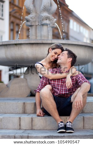 Affectionate young couple sitting by the fountain - stock photo