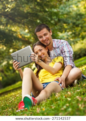 Affectionate young couple sitting in park with tablet.  - stock photo