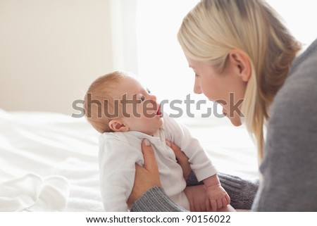 Affectionate young mom holding her newborn - stock photo