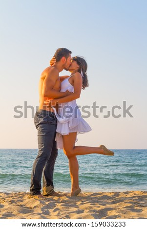 Affectionately embraced and tenderly kissing, a young couple enjoys a mid summer late afternoon, on a wet sandy beach. - stock photo