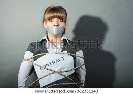 Afraid businesswoman bound by contract terms and conditions with mouth taped shut. Scared woman tied to chair become slave. Business and law concept. - stock photo