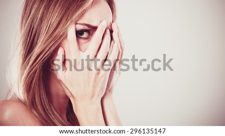 Afraid frightened woman peeking through her fingers on grey. Shy teen girl covering face with hands. - stock photo
