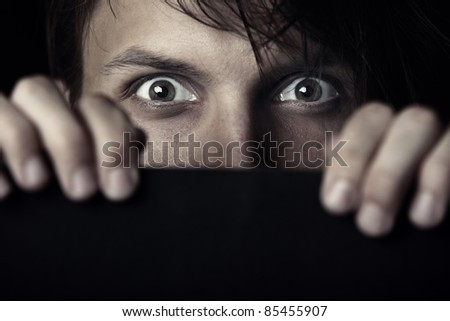 Afraid human hiding behind the dark board - stock photo