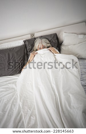 Afraid woman alone in the bedroom - stock photo