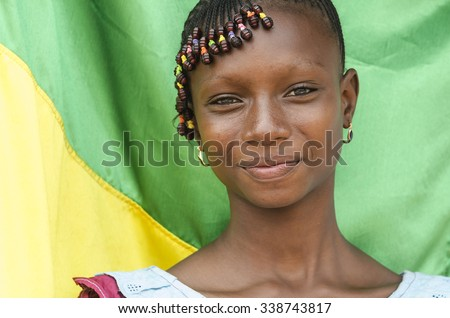 Africa Girl Posing in Front of Malian Flag - stock photo