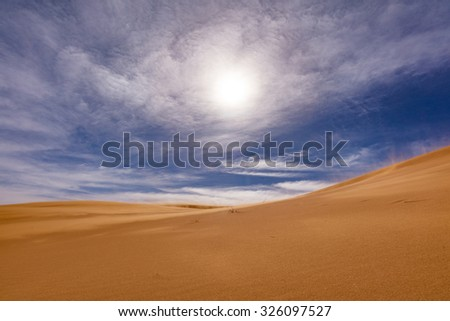 Africa - view of Erg Chebbi Dunes in Morroco- Sahara Desert during strong wind, visible sand particules in sky (not noise) -  backlight effect - stock photo