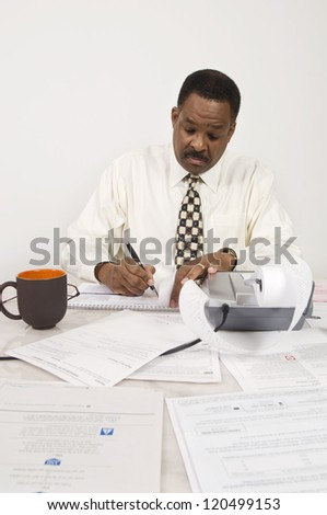 African American accountant writing on desk with expense receipt - stock photo