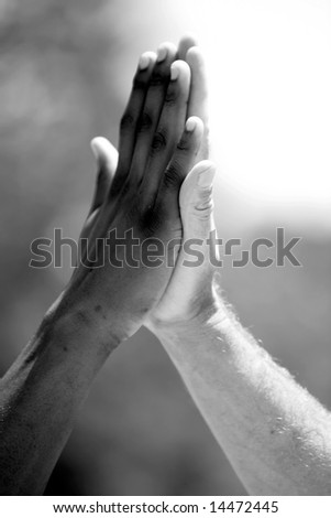 "african american and European american men do a ""high five"" hand clap outside in black and white - stock photo"