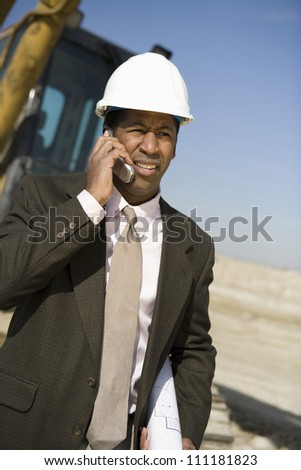 African American architect wearing hard hat as he's on call at construction site - stock photo