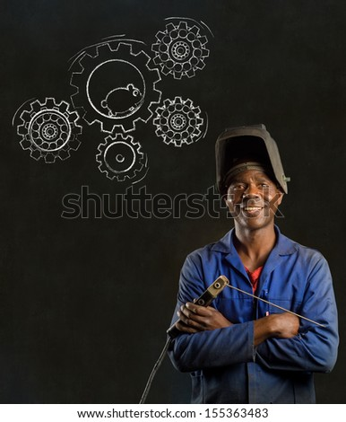 African American black man industrial worker with chalk hamster gears on a blackboard background - stock photo