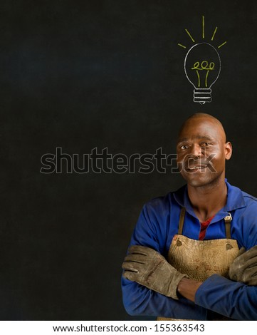 African American black man industrial worker with chalk light bulb on a blackboard background - stock photo