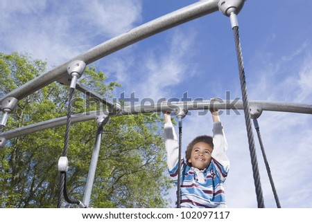 African American boy playing on jungle gym - stock photo