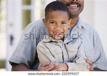 African American boy sitting on father's lap - stock photo