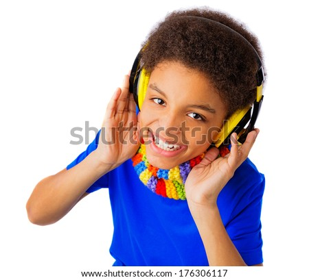 African American boy, teenager smiling and listening to music with yellow headset and colorful scarf. Over white background, isolated, with copy space. - stock photo