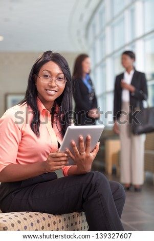 african-american business woman sitting in lobby with computer tablet, looking at camera, smiling, two business women in background - stock photo