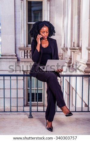 African American Business Woman working in New York. Young black college student with braid hairstyle sitting on railing, working on laptop computer, calling on phone. Filtered look with purple tint. - stock photo