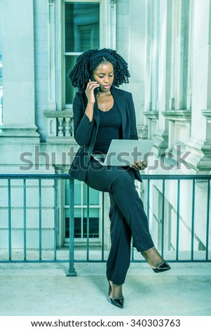 African American Business Woman working in New York. Young black college student with braid hairstyle sitting on railing, working on laptop computer, calling on phone. Filtered look with cyan tint. - stock photo