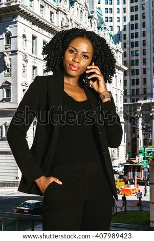 African American Business Woman working in New York. Young black college student with braid hairstyle standing by vintage office building, listening, talking on cell phone. Instagram filtered effect.  - stock photo