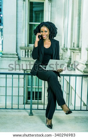 African American Business Woman working in New York. Young black lady with braid hairstyle sitting on railing, smiling, working on laptop computer, making phone call. Filtered look with green tint.  - stock photo